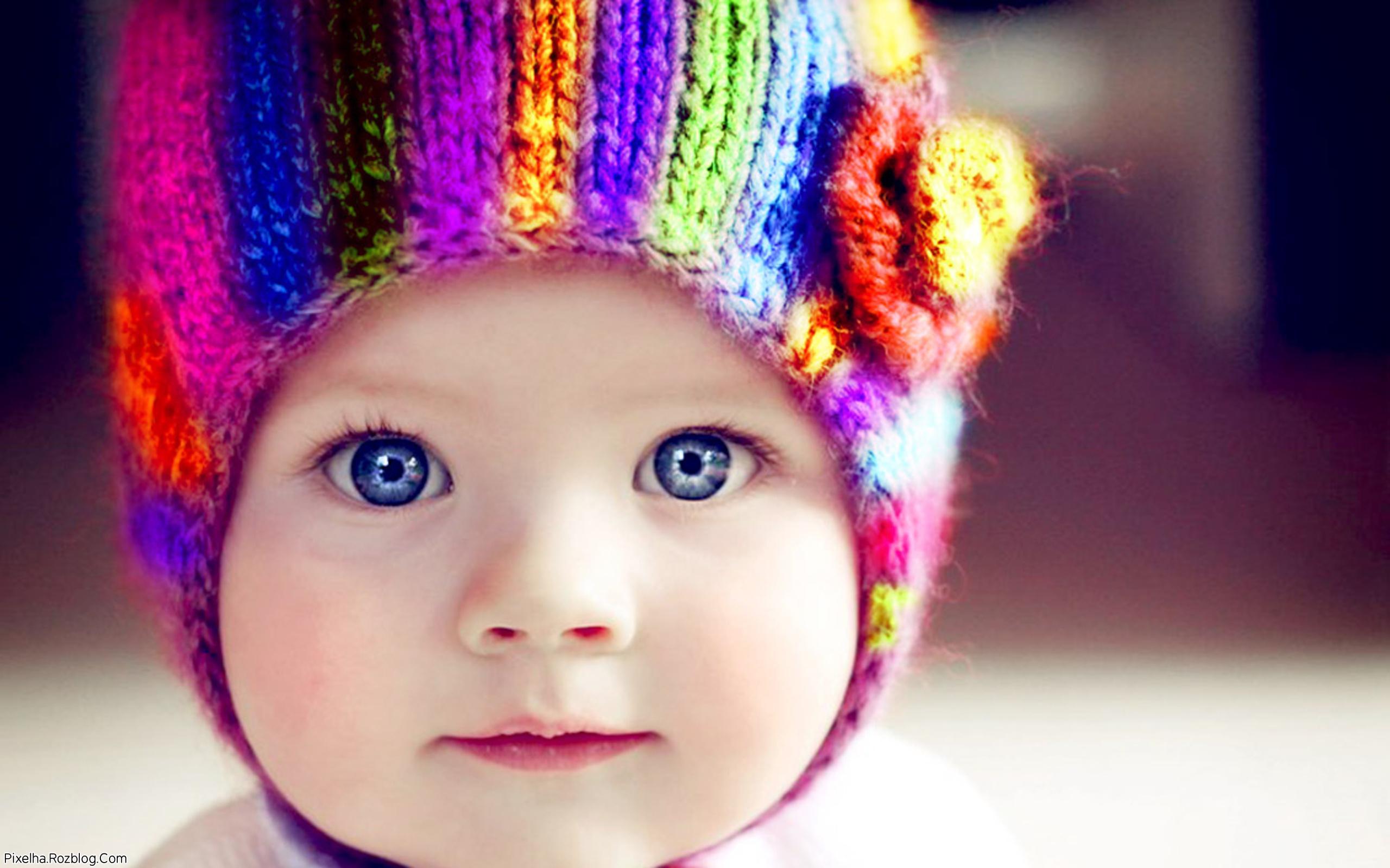 پسربچه بامزه با کلاه رنگارنگ و چشمان آبی