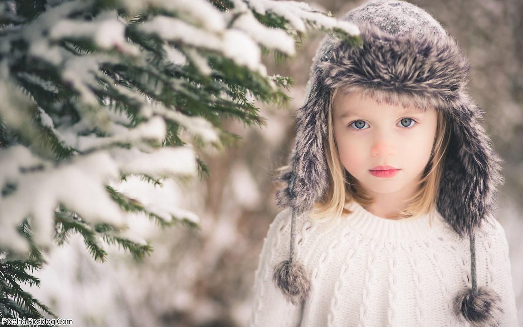 دختربچه بامزه در کنار برف زمستانی