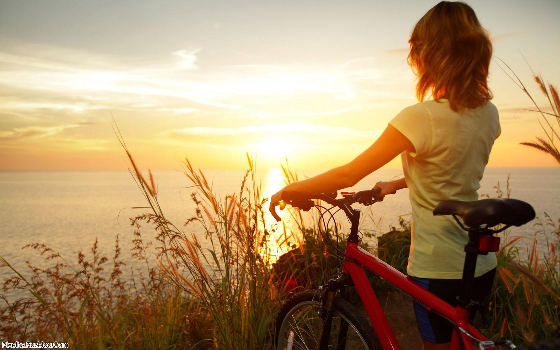 دختر دوچرخه سوار در حال تماشای غروب خورشید