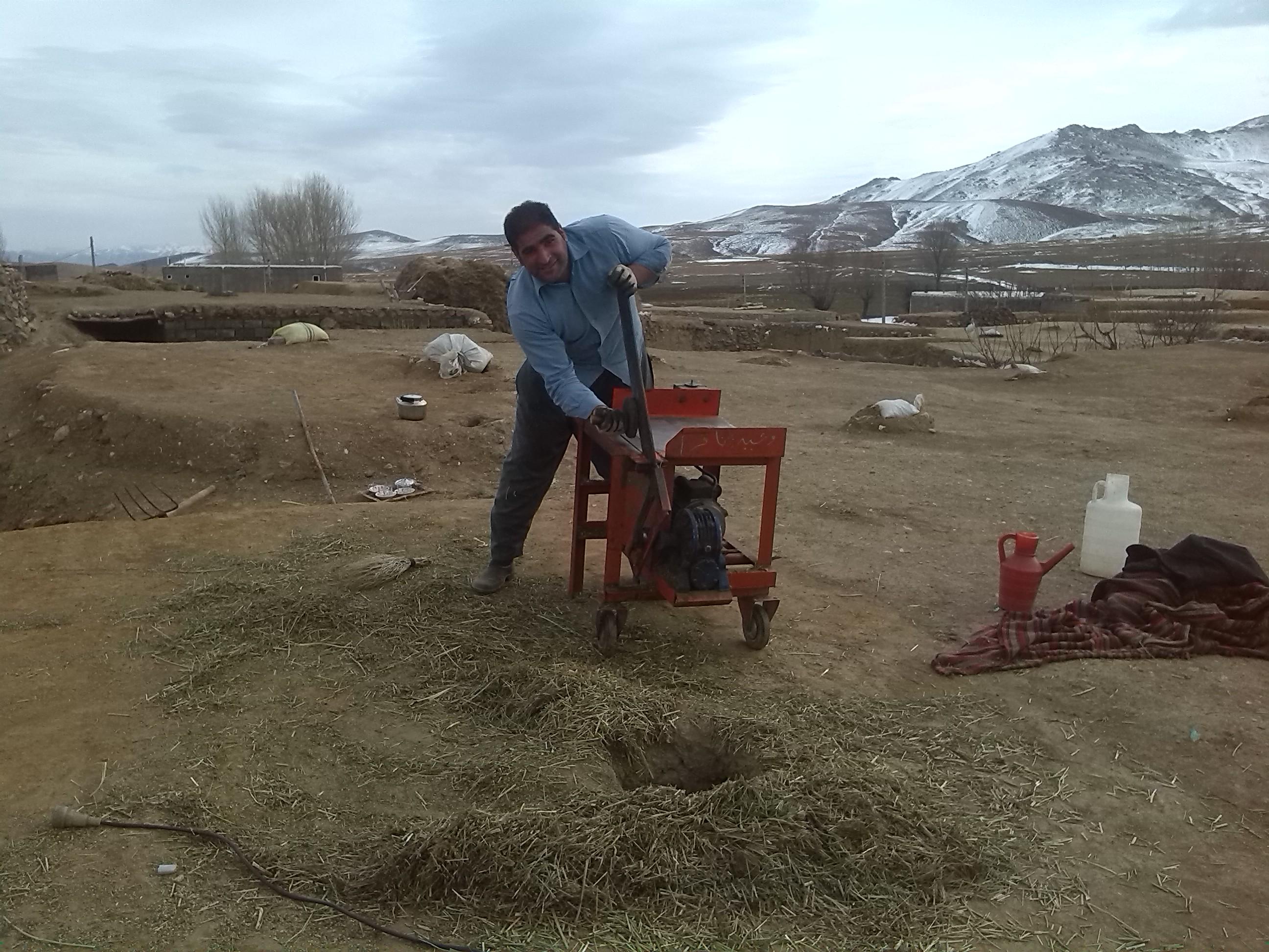 عکس از خرد کردن علوفه در روستا برای حیوانات