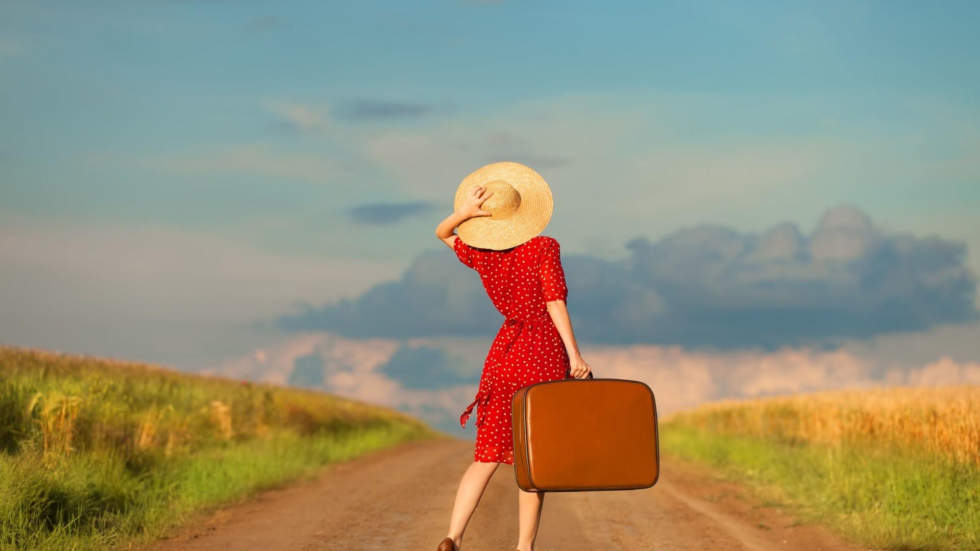 دختری با لباس قرمز و کلاه زرد و چمدان به دست