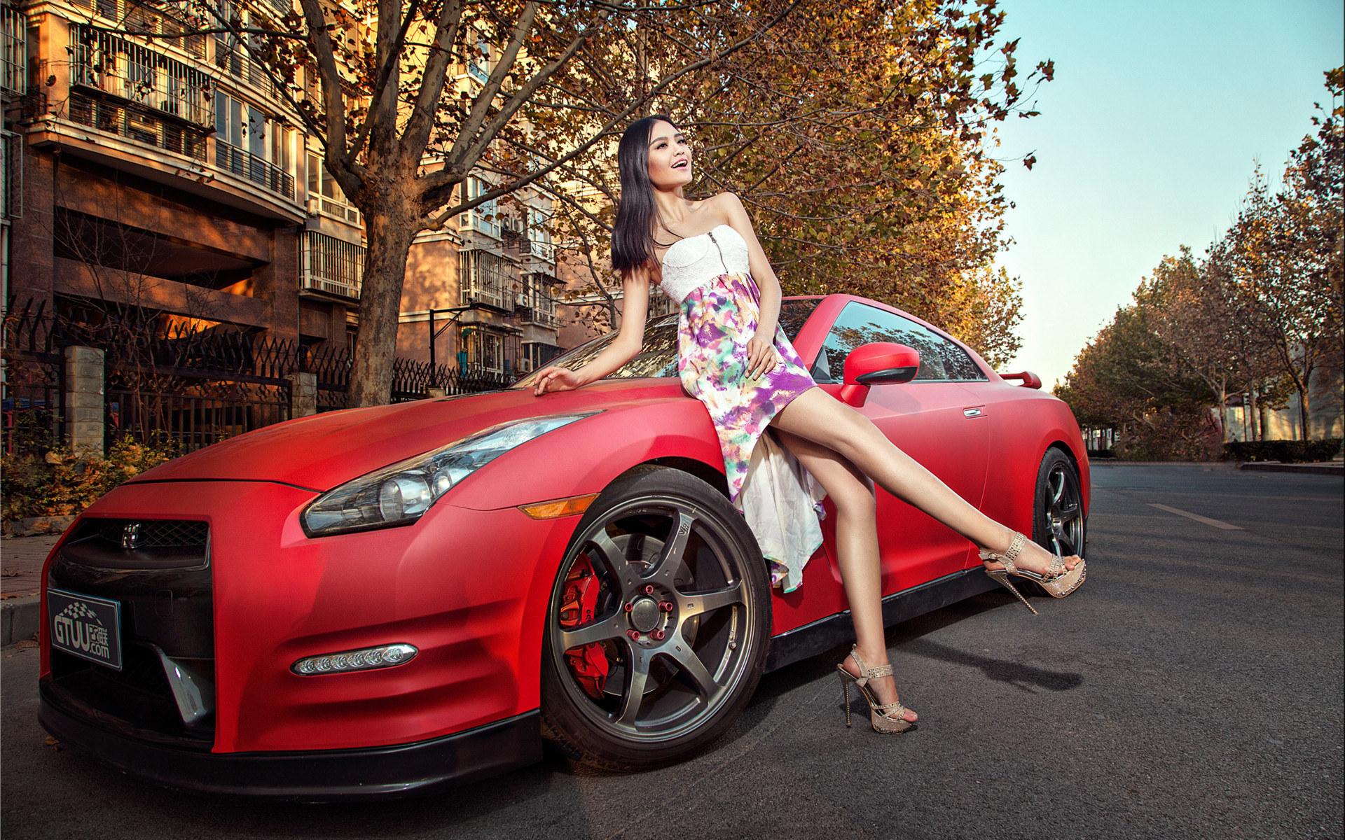 دختر آسیایی کنار ماشین نیسان قرمز