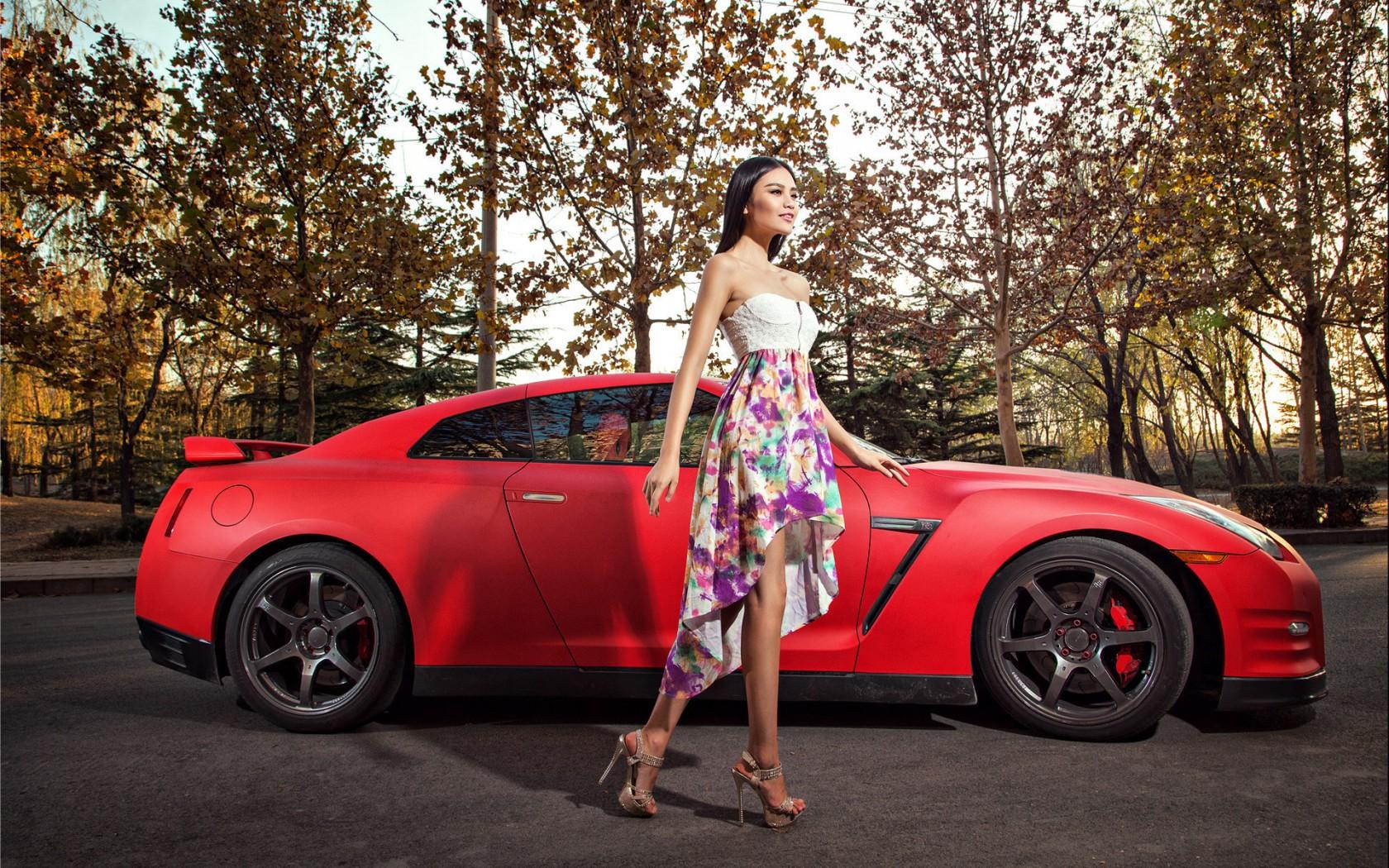 دختر آسیایی کنار ماشین نیسان قرمز جی آر تی