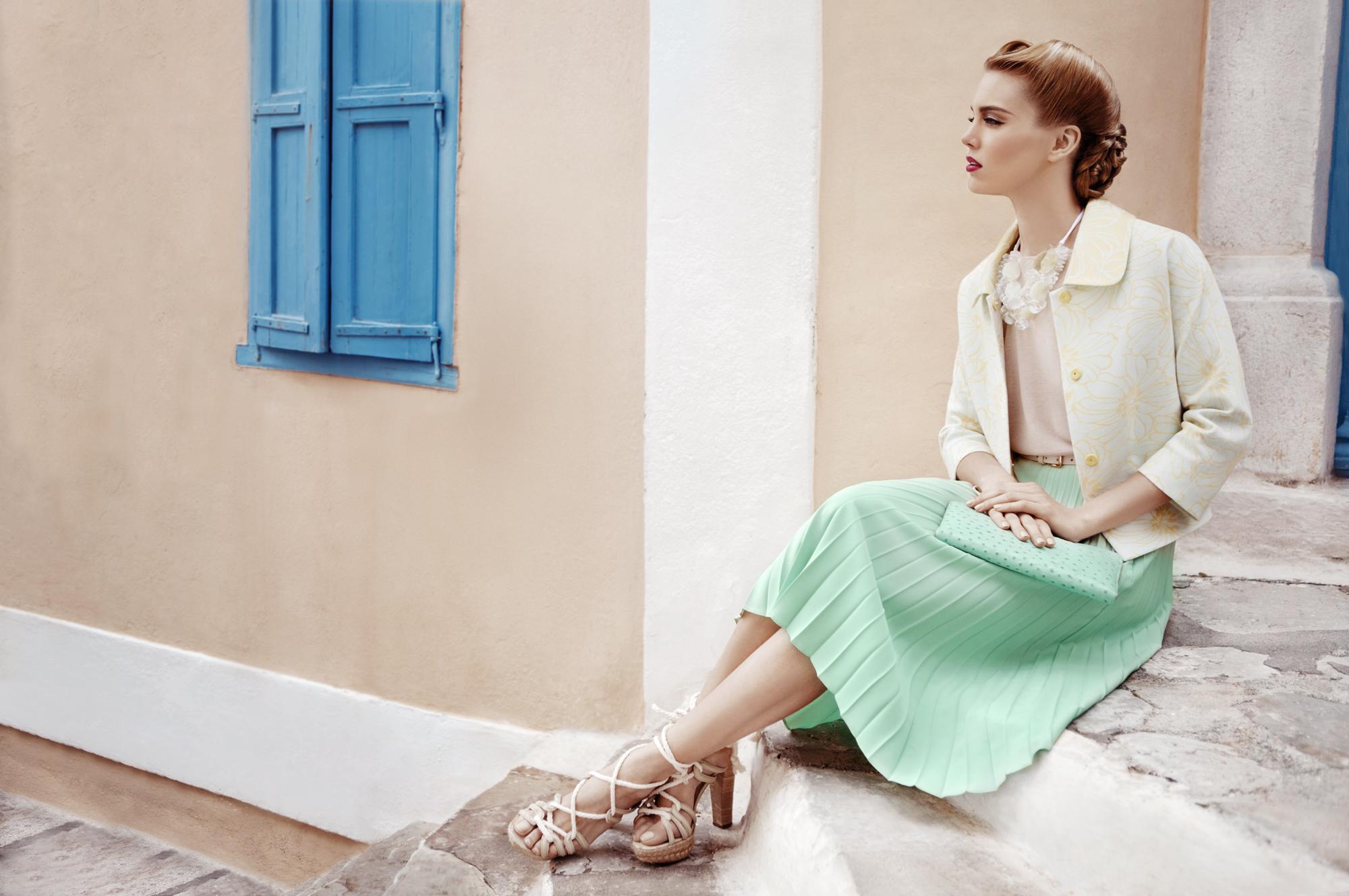 عکس دختر نشسته روی پله با دامن و کیف پسته ای