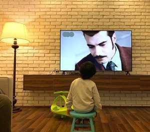 پسر محسن تنابنده در حال تماشاي تلوزيون